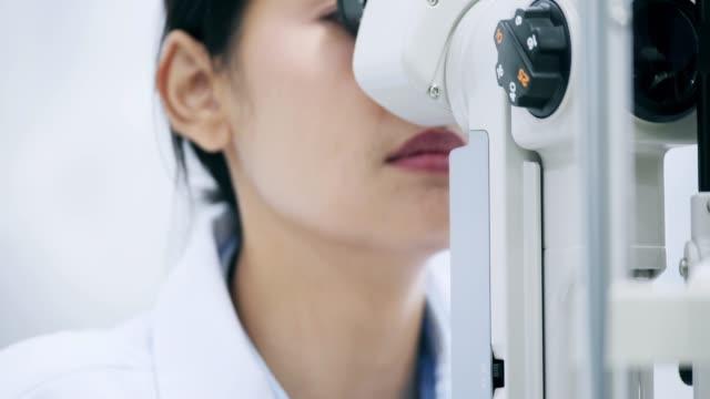 stockvideo's en b-roll-footage met oogarts controleert de ogen van de vrouw. close-up. - opticien