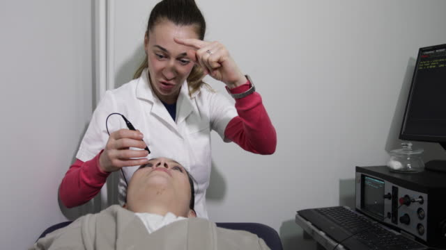 ophthalmologist measuring intraocular pressure of woman in clinic - ophthalmologist stock videos and b-roll footage