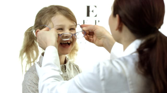 hd: ophthalmologist putting glasses on little girl - spectacles stock videos & royalty-free footage