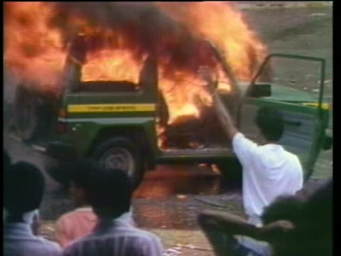opponents of general manuel noriega throw rocks, overturn cars and cheer near a burning car during a riot. - パナマ点の映像素材/bロール