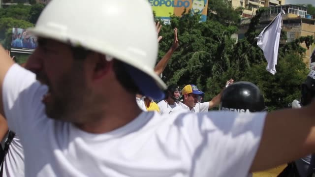 Opposition activists clash with the riot police as they block the Francisco Fajardo highway in Caracas during a demonstration against President...
