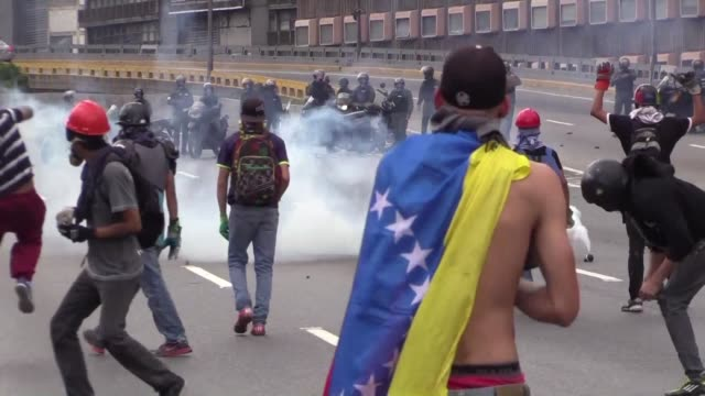 opposition demonstrators in caracas clash with the members of the national guard who fired tear gas canisters during protests saturday - bombola video stock e b–roll