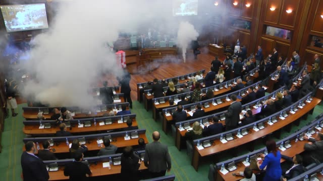 Opposition lawmakers throws a tear gas canister disrupting a parliamentary session in Kosovo capital Pristina on March 21 2018 Kosovo's Parliament...