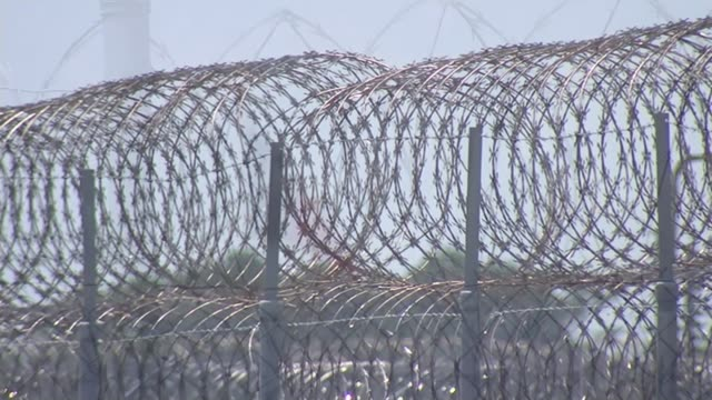 opposition to death penalty; usa: texas: texas state penitentiary: ext barbed wire fence texas flag seen through barbed wire state penitentiary with... - hinrichtung stock-videos und b-roll-filmmaterial
