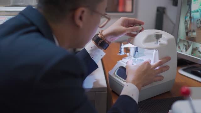 optician making eyeglasses ophthalmology instrument measuring glass on eyewear - lens optical instrument stock videos & royalty-free footage