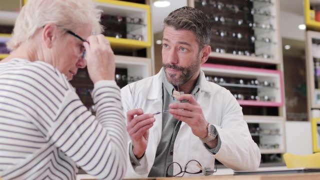 vidéos et rushes de optician suggesting frames to customer - opticien