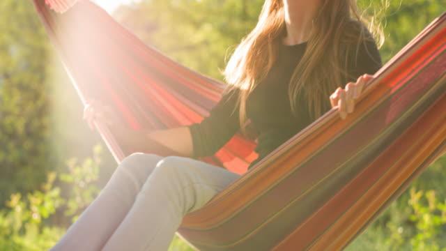 vidéos et rushes de femme optimiste se balançant dans un hamac dans le jardin en été - balançoire