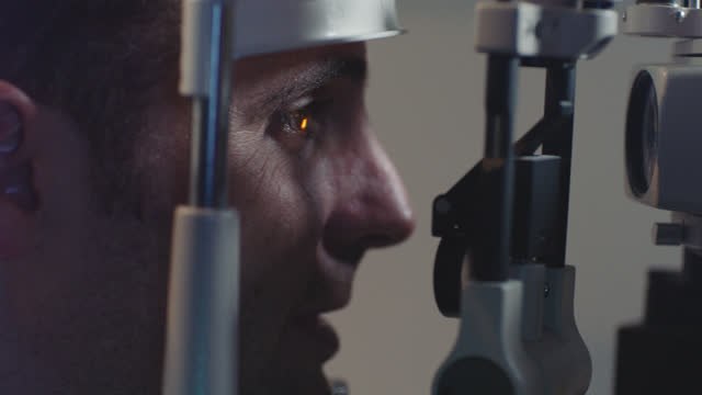 stockvideo's en b-roll-footage met cu. optometrist adjusts head rest and shines bright light on eye as patient undergoes slit lamp exam. - oogmeetkunde