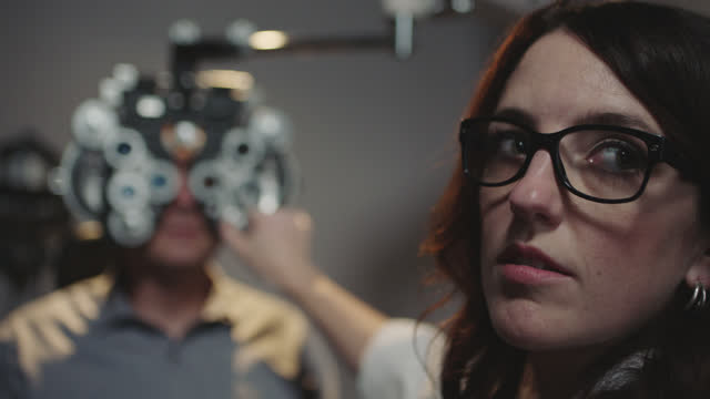 MS OTS. Optometrist adjusts phoropter on patient and turns her head to glance at chart during eye exam.