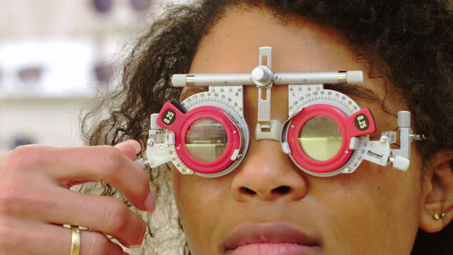 optometrist checking eyesight of a female client - lens optical instrument stock videos & royalty-free footage