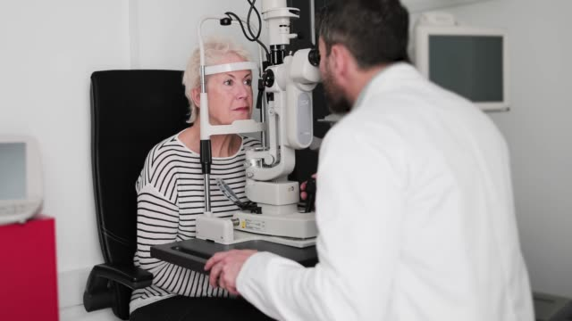 vidéos et rushes de optometrist discussing results of eye test with customer - opticien
