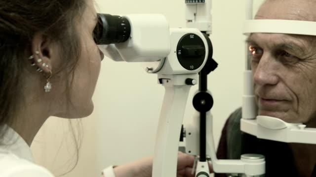 Optometrist examines man's eyesight