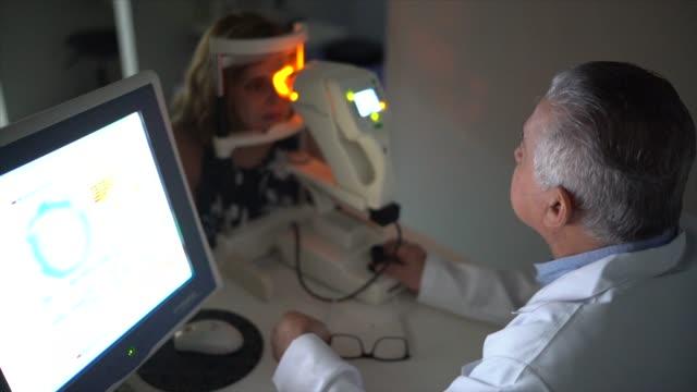 optometrist examing patient's eyes - retina stock videos & royalty-free footage