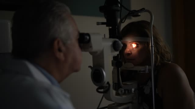 optometrist examing patient's eyes - optical equipment stock videos & royalty-free footage