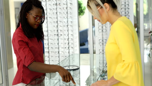 optometrist helping client to choose  eyeglasses - visual merchandising stock videos and b-roll footage
