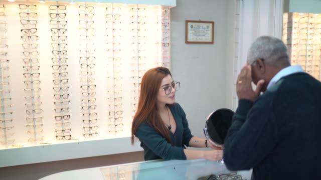 vídeos de stock, filmes e b-roll de cliente de ajuda de optometrist que tenta em alguns vidros - loja
