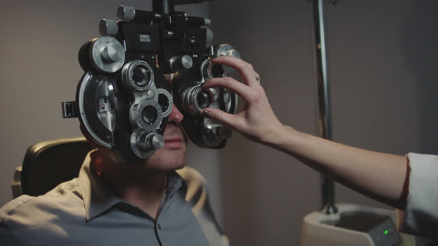 ms. optometrist switches lenses and adjusts phoropter on patient. - lens optical instrument stock videos & royalty-free footage