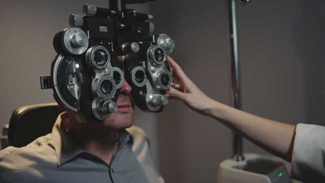 ms. optometrist switches lenses and adjusts phoropter to determine precise eyeglass presciption for patient. - lens optical instrument stock videos & royalty-free footage