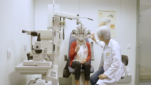 optometrist using phoropter to check eyesight of patient - lens optical instrument stock videos & royalty-free footage