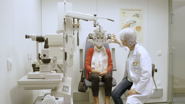 optometrist using phoropter to check patient eyes in clinic - lens optical instrument stock videos & royalty-free footage