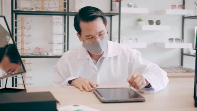 optometrist using tablet for write a prescription - stock video - lens optical instrument stock videos & royalty-free footage