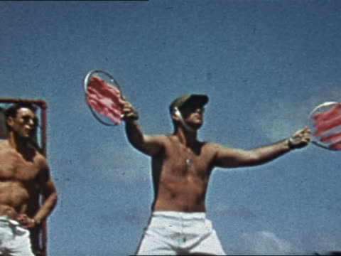 1943 or 1944 WWII landing signal officer waving discs to F6F flying overhead on USS Yorktown