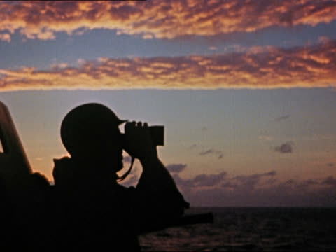 1943 or 1944 wwii plane spotter on uss yorktown looking through binoculars and pointing at sunrise - uss yorktown stock videos & royalty-free footage