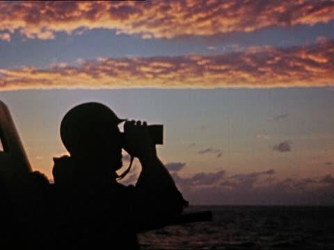 1943 or 1944 wwii plane spotter on uss yorktown looking through binoculars and pointing at sunrise - binoculars stock videos & royalty-free footage