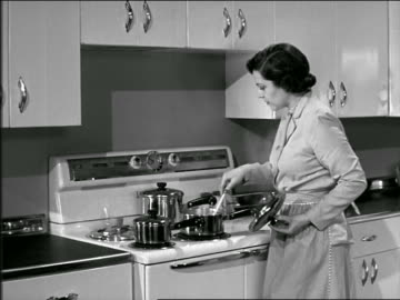 b/w 1946 or 1951 housewife stirring food in pot on stove - kitchen stock videos & royalty-free footage