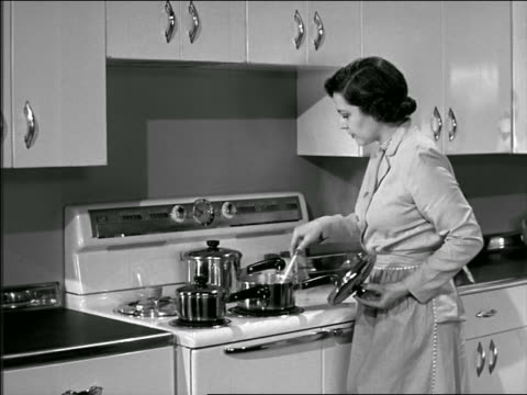 b/w 1946 or 1951 housewife stirring food in pot on stove - 1950 stock-videos und b-roll-filmmaterial
