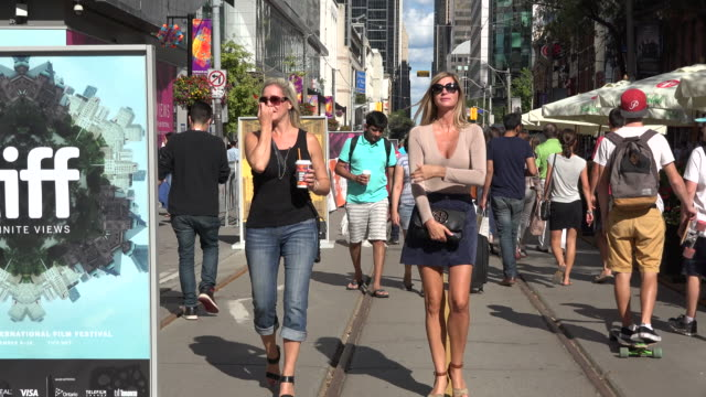 TIFF or Toronto International Film Festival Zoom out from pedestrians enjoying the new vehicle closed Festival Street Festival Street is the...