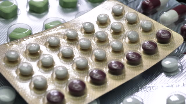 oral contraceptive pill on pharmacy with colorful pills strips background - contraceptive stock videos & royalty-free footage