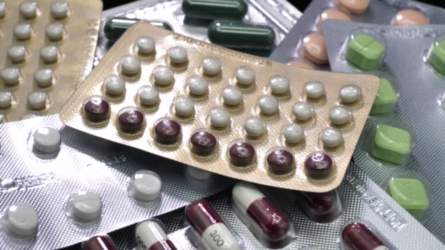 oral contraceptive pill on pharmacy with colorful pills strips background - menstruation stock videos & royalty-free footage