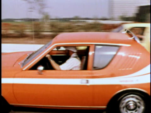 montage orange amc gremlin driving on road/ usa - orange colour stock videos & royalty-free footage