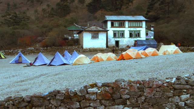 orange and blue tents in front of a white building in nepal. - base camp stock videos & royalty-free footage