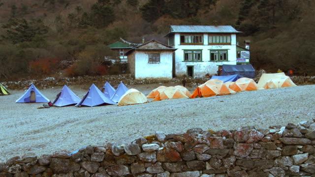 orange and blue tents in front of a white building in nepal. - basläger bildbanksvideor och videomaterial från bakom kulisserna