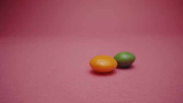 ピンクの背景にオレンジと緑のゼリービーン - ジェリービーンズ点の映像素材/bロール