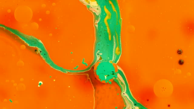 Orange and green sphere pops disappears vibrant bright paint and oil color swirls entropy