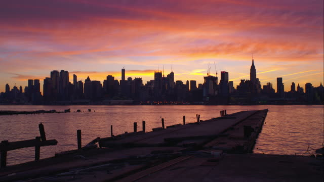 stockvideo's en b-roll-footage met orange and purple clouds over midtown manhattan - stilstaande camera
