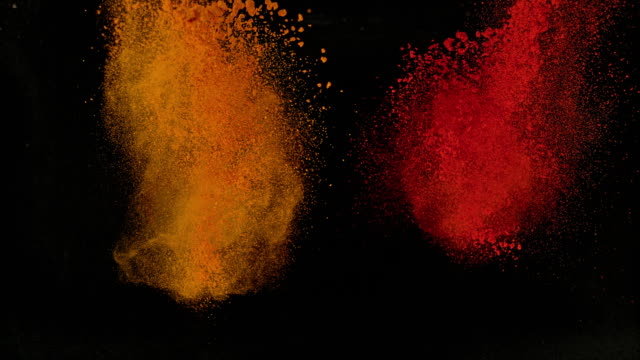 slo mo ld orange and red powdered spices exploding out of black background - spice stock videos & royalty-free footage