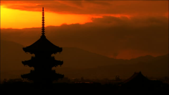 orange and red sunset, silhouette of pagoda in foreground - pagoda点の映像素材/bロール