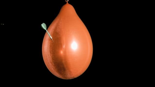 Orange balloon in super slow motion exploding