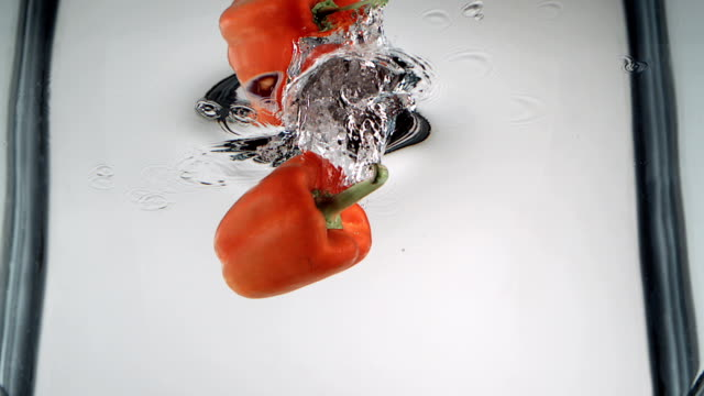 orange bell pepper planschen in wasser - orangefarbige paprika stock-videos und b-roll-filmmaterial