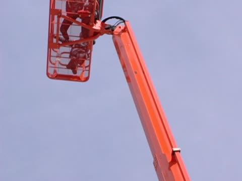 vidéos et rushes de orange boom étendant au cadre - harnais de sécurité