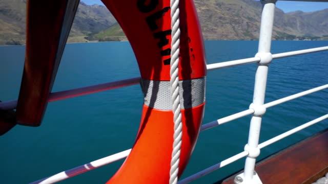 orange buoy on railing of ship