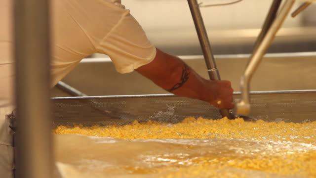 vídeos y material grabado en eventos de stock de orange cheese curds in a large mixing tank - queso