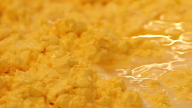 Orange cheese curds in a large mixing tank