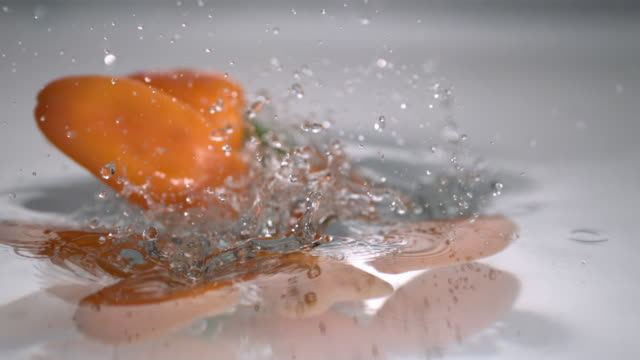 cu slo mo orange chili peppers falling into water / new jersey, usa - orange new jersey stock videos & royalty-free footage