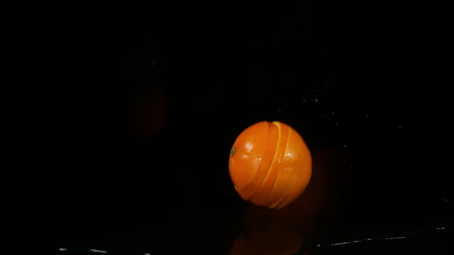 orange, citrus sinensis, fruit falling into water against black background, slow motion 4k - citrus fruit stock videos and b-roll footage