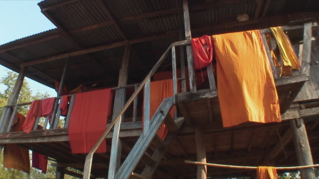 vídeos de stock e filmes b-roll de ms la orange clothes hanging on porch, luang prabang, laos - toalha